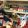 Loaves and Fishes Food Pantry volunteer Beckey Zolla works with client Julie Smith on Friday afternoon helping her get the food she needs. SUN/JOHN LOVE