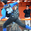 Bennett players try to keep warm while watching the game.  B. Novak pitches