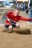 Long jump in the cold (hands tucked into sleeves.