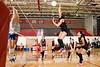 Kristy Cooper spikes against University Blockers as her team looks on
