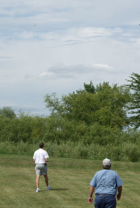 Mark Joseph pilots his Arcie II radio-controlled boost glider while Chris Deem looks on.  The glider is visible in the upper left of the picture (better in the Large or Original size view).  Photo by Greg Smith.