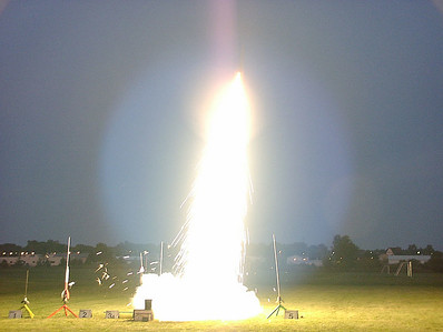 Shot at dusk, this shows Gary Buck's Phoenix taking off with one of the last Rocketflite Silver Streak G160 motors.  Check out the broad circle of illumination on the ground from this rocket exhaust!  The rocket is barely visible at the top of the flame trail.  Sensor overload produced the purplish streak at the top of the image.  Photo by Greg Smith at the September 11, 2004 CIA launch.