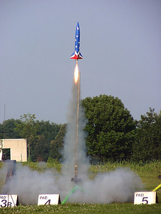 Greg Smith's red, white and blue LOC Onyx lifts off with an Aerotech F25-6 motor.  Photo by Greg Smith.