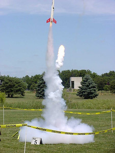 Liftoff of Chris Deem's BATFE Special with a cluster of four D11 and four E9 motors.  Two of the D11s failed at ignition, damaging the rocket, but it recovered and made a safe, stable flight.  This is image 8 of a series of 16 taken at 15 frames per second.  Photo by Greg Smith.