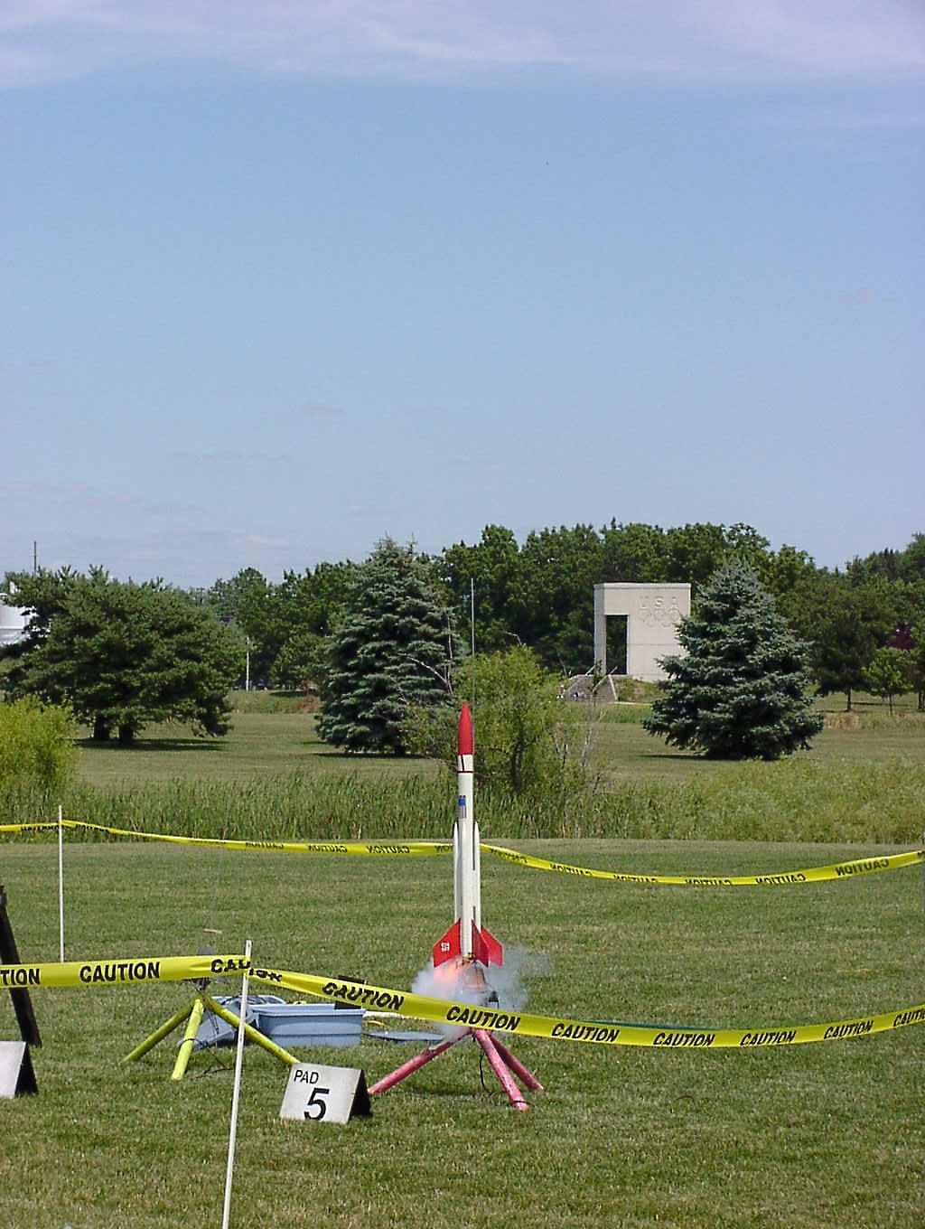 Liftoff of Chris Deem's BATFE Special with a cluster of four D11 and four E9 motors.  Two of the D11s failed at ignition, damaging the rocket, but it recovered and made a safe, stable flight.  This is image 1 of a series of 16 taken at 15 frames per second.  Photo by Greg Smith.