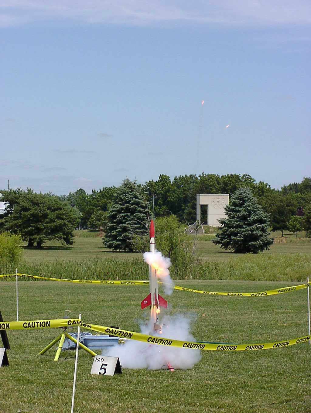 Liftoff of Chris Deem's BATFE Special with a cluster of four D11 and four E9 motors.  Two of the D11s failed at ignition, damaging the rocket, but it recovered and made a safe, stable flight.  This is image 4 of a series of 16 taken at 15 frames per second.  Photo by Greg Smith.