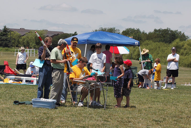 Crowd around the launch control table waiting to be assigned a pad to launch their rockets.  Photo by Alan Carroll.