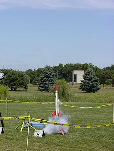 Liftoff of Chris Deem's BATFE Special with a cluster of four D11 and four E9 motors.  Two of the D11s failed at ignition, damaging the rocket, but it recovered and made a safe, stable flight.  This is image 3 of a series of 16 taken at 15 frames per second.  Photo by Greg Smith.