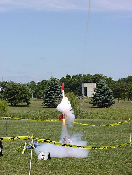 Liftoff of Chris Deem's BATFE Special with a cluster of four D11 and four E9 motors.  Two of the D11s failed at ignition, damaging the rocket, but it recovered and made a safe, stable flight.  This is image 5 of a series of 16 taken at 15 frames per second.  Photo by Greg Smith.