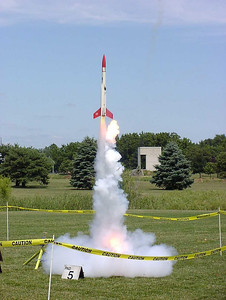 Liftoff of Chris Deem's BATFE Special with a cluster of four D11 and four E9 motors.  Two of the D11s failed at ignition, damaging the rocket, but it recovered and made a safe, stable flight.  This is image 7 of a series of 16 taken at 15 frames per second.  Photo by Greg Smith.