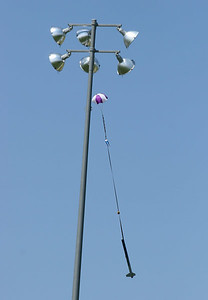 Nick's Callisto descends in front of one of the lights at the Dodds Park softball complex, just north of the launch location.  (Despite appearances, the rocket is on the near side of the pole.)  Photo by Greg Smith