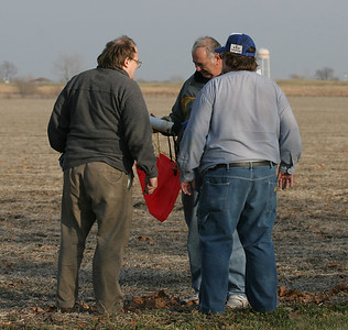 "Lon and Chris look over the remains of Mike's Astrobee-D after its ""lawn dart"" landing.  Photo by Greg Smith"