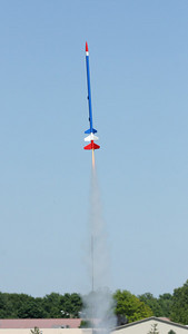 Launch of Jonathan Sivier's Comanche-3, a three-stage model painted red, white and blue, with a D12-0 booster.  Photo by Greg Smith
