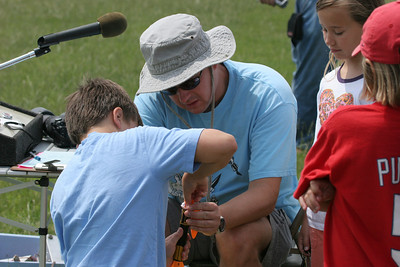 Robert Brunner helps a young modeler load the parachute in his Alpha III.  Photo by Greg Smith
