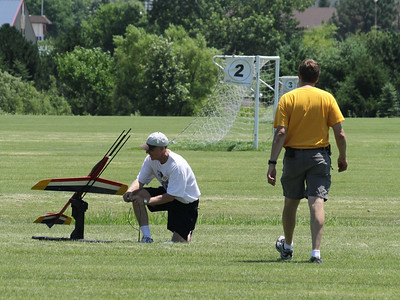 Mark Joseph approaches the pad to help Dave Harris as he prepares the igniter in his Aerotech Phoenix radio-controlled rocket glider.  Photo by Greg Smith