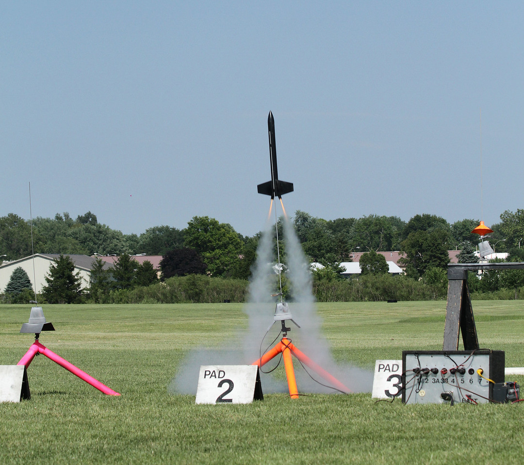Liftoff of a FlisKits Deuces Wild with two B6-4 motors.  Notice how the motors are canted outward with their thrust vectors intersecting the rocket's center of gravity.  This should make it fly straighter even if one motor fails to ignite (although both lit just fine for this flight).  Photo by Greg Smith