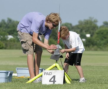 Adam Joseph helps a young rocketeer get his rocket loaded and hooked up on the pad.  Photo by Greg Smith