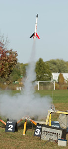 Greg Smith's reproduction of an Estes Astron Cobra lifts off with a cluster of three C6-7 motors, all ignited successfully.  The nose cone, payload and transition sections are original parts from a kit built in 1969, but the main body and fins were replaced (for the second time) in the summer of 2016.  Photo by Greg Smith