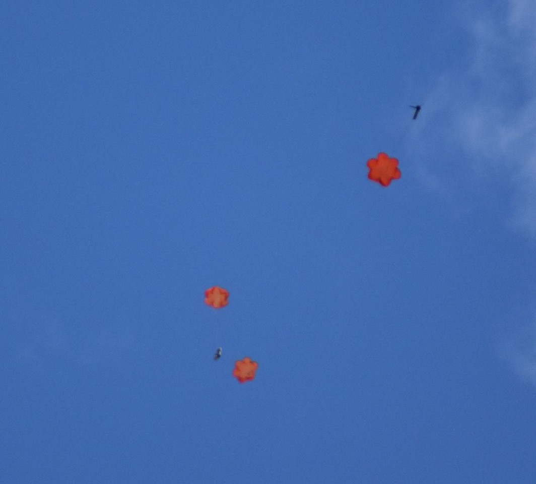 The camera under two parachutes, the booster under one.