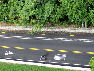 a woman living dangerously, playing with an adult version of a Big Wheel in the driving lane rather than the bike lane, seen from the top of the William Penn Memorial Firetower, September 16, 2017