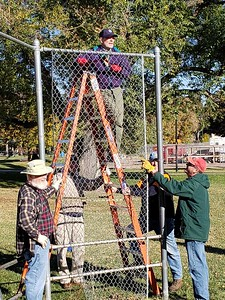 Rotarian Stacy Plemmons (on ladder), who organized the Rotary workday, readies backstop fence for removal.