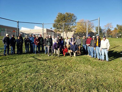 Rotarians from Fort Collins and other community volunteers gather around the backstop to be removed as part of the renovation of the Eastside Community Park.