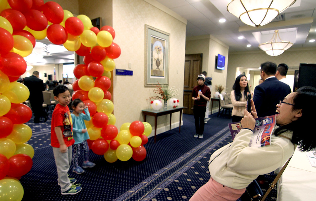 . Nhat Le of Boston, leans way back to get her kids, John & Jane Wu, in a photo at the Vietnamese Lunar New Year celebration. SUN/David H.Brow