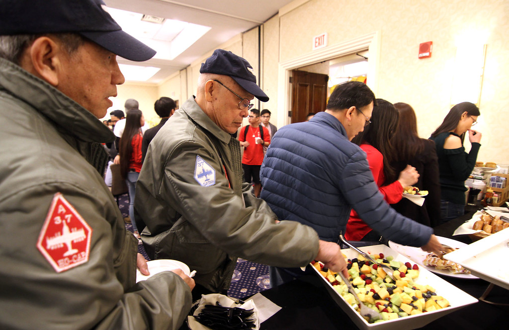 . Folks at the Vietnamese Lunar New Year celebration hitting the food line, in front are some members of the South Vietnam air force fighter pilots veterans. SUN/David H.Brow