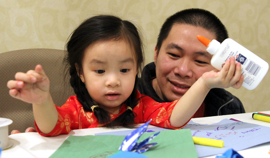 . Making paper crafts at the Vietnamese Lunar New Year celebration is Vivien Nguyen, 30 months old and her dad, Michael Nguyen of Lawrence. SUN/David H.Brow