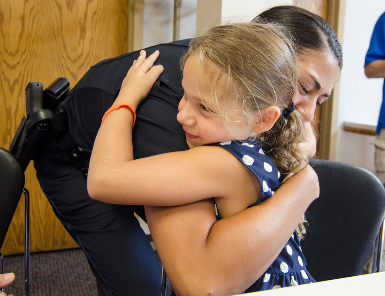 Jazmin Foshie, 6, gives a hug to Officer Julie Salas after presenting her with a keychain as a token of appreciation last week. Members of four local churches, Elm Street Community Church, Horizon Fellowship, Nashua Valley Christian Church and New Creation Community Church, joined together to create cards, a poster, and the keychains to show their support for the Fitchburg Police Department. SENTINEL & ENTERPRISE / Ashley Green