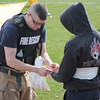 KRISTI GARABRANDT - THE NEWS-HERALD<br /> <br /> Eastlake firefighter places a tracking bracelet on a victim during the training exercise. The bracelet allows first responders to keep track of which hospital each victim is being transported to, and