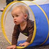 Eric Bonzar—The Morning Journal<br /> One-year-old Logan Kuhns works on his sliding technique by crawling through the tunnel during the Elyria Public Library System's West River Branch Baseball Party, April 20, 2016.