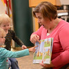 """Eric Bonzar—The Morning Journal<br /> Three-year-old Kylie Kuhns shows Jenny Beno, youth services librarian, where the baseball went during story time of the Elyria Public Library System's West River Branch Baseball Party, April 20, 2016. Beno read """"Hit The Ball Duck,"""" by Jez Alborough, to the kids."""