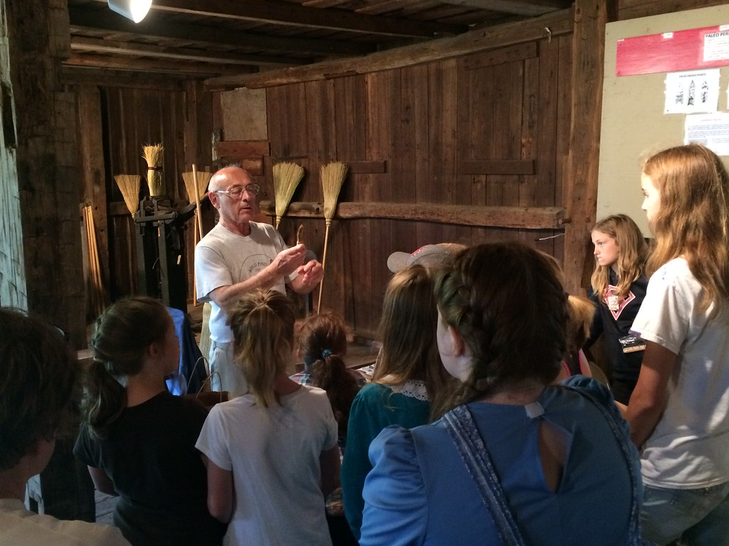 . Chad Felton � The News-Herald  Campers watch as prehistorian and program instructor Mike Fath holds a spearhead at Century Village Museum\'s 45th Pioneer School in Burton Village. Campers participated in a wide array of activities which embrace the customs of early Geauga County settlers.