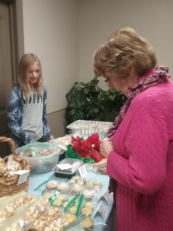. Margaret Lanese (r) of Concord Township peruses a large selection of goodies while St. Gabriel School student Gabriella Bedrick stands by to assist. {Jean Bonchak for The News-Herald}
