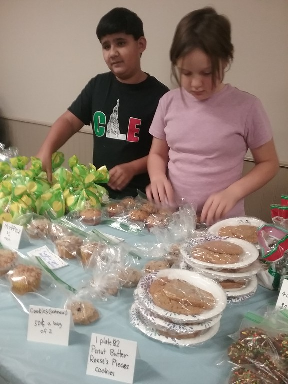 . St. Gabriel School students Andrew Zarbo and Elizabeth Horne organize an array of goods for the fundraiser. {Jean Bonchak for The News-Herald}