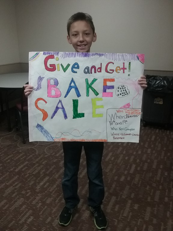 . Handmade posters advertising the sale were an important element drawing customers to visit the bake sale. St. Gabriel School student Robert Bonchak displays one of the many signs created by the fourth grade classes. {Jean Bonchak for The News-Herald}