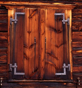 Wooden shutter securing a window of an old farm house