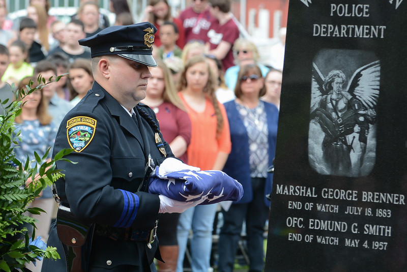 Eric Bonzar—The Morning Journal<br /> A member of the Elyria Police Department Honor Guard places a flag of honor at the Wellington Safety Forces Memorial, May 11, 2016. Officers and civilians throughout Lorain County gathered at Howk Memorial Park to remember those officers who lost their lives in the line of duty, during the Lorain County Police Memorial event.