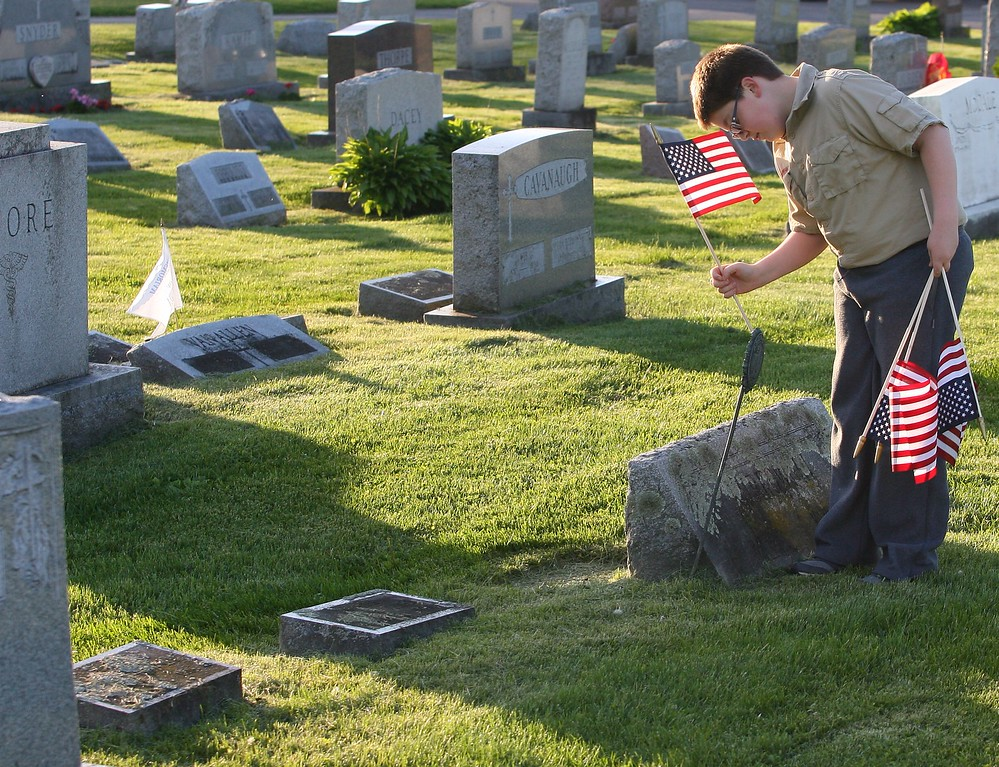 . Boy Scout Troop 23 member Jack Reese ,  12, along with fellow troop members place more than 400 America Flag at the graves  of veterans  at St. Patrick\'s cemetery in Oneida on Wednesday, May 20, 2015.  JOHN HAEGER-ONEIDA DAILY DISPATCH @ONEIDAPHOTO ON TWITTER