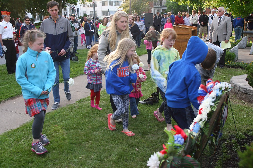 . People place flowers at the base of the memorial during the the city of Oneida  Memorial Day service on Friday. May 22, 2015. JOHN HAEGER-ONEIDA DAILY DISPATCH @ONEIDAPHOTO ON TWITTER
