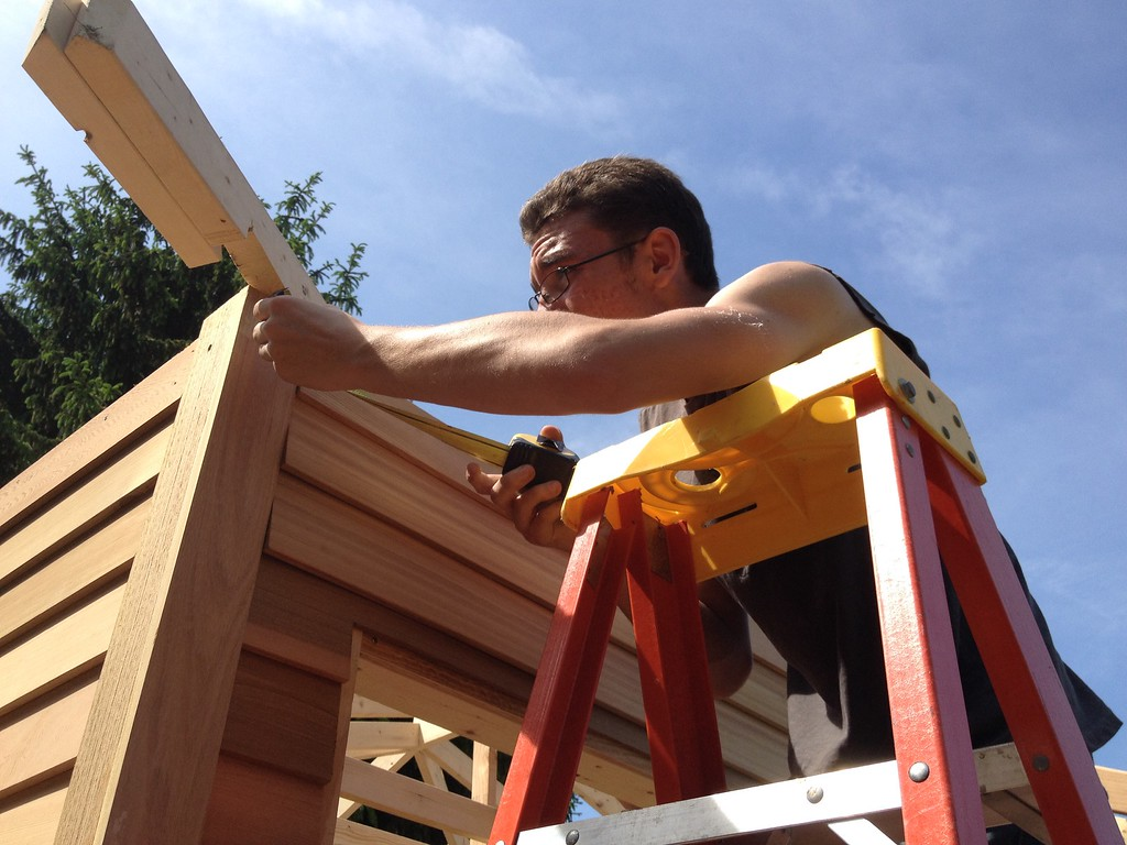 . Oneida carpentry student Dylan Webb takes a measurement on roof line on the pool house structure on Friday, May 29, 2015. JOHN HAEGER-ONEIDA DAILY DISPATCH @ONEIDAPHOTO ON TWITTER