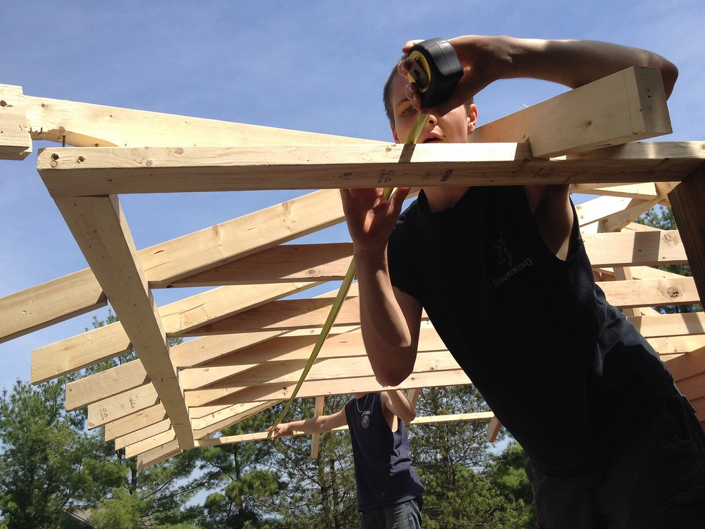 . Oneida carpentry student Tim Wimett takes a measurement on roof line on the pool house structure on Friday, May 29, 2015. JOHN HAEGER-ONEIDA DAILY DISPATCH @ONEIDAPHOTO ON TWITTER