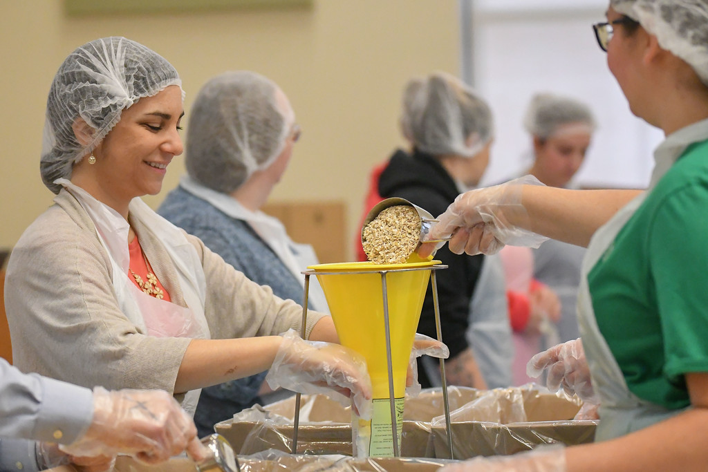 . Eric Bonzar�The Morning Journal<br> Academic Advisor Allison Groesch works with students and coworkers to package fortified apple and cinnamon oatmeal, during the Americorps\' Martin Luther King Jr. Day Meal Packaging event, Jan. 22, 2018. Volunteers came to Lorain County Community College\'s College Center, donating an hour of their time to help package the warm breakfast cereal, in an effort to combat food insecurity in Lorain County.