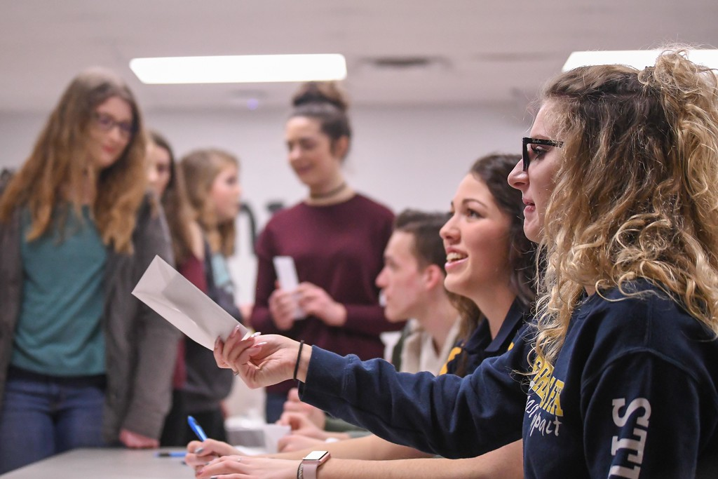 . Eric Bonzar�The Morning Journal<br> Firelands Future Farmers of America member Sarah Stitchick, 17, passes out envelopes with class assignments during the group\'s Hunger Breakfast simulation, Feb. 6, 2018. As part of the simulation, students were given a fictitious name, economic status and financial situation. They were then placed into economic classes which included upper, middle, low and poverty and then tasked with purchasing menu items based on the money they had.