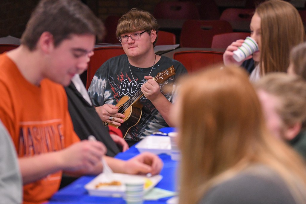 ". Eric Bonzar�The Morning Journal<br> As ""middle class\"" students enjoy breakfast, 17-year-old \""homeless\"" student David Nary busks to earn enough money to buy his own, during Firelands Future Farmers of America\'s Hunger Breakfast simulation, Feb. 6, 2018. The simulation was held to educate student leaders about food insecurity in their school and community."