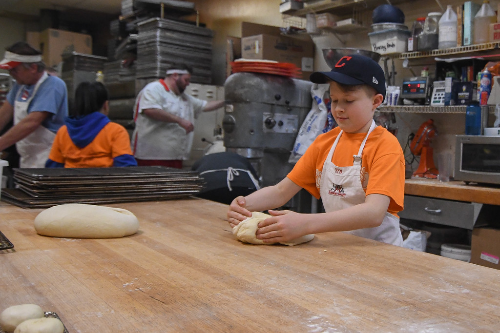 . Eric Bonzar�The Morning Journal<br> Ten-year-old Ben Kiedrowski tries his hand at pounding out P�czki dough, Feb. 13, 2018.