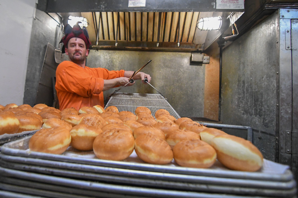 . Eric Bonzar�The Morning Journal<br> P�czki, fresh from the fryer, slid onto a tray and ready for filling, Feb. 13, 2018.