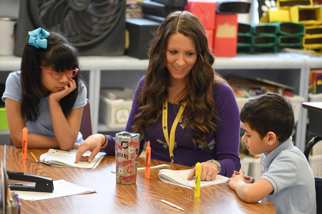 . Eric Bonzar�The Morning Journal<br> Third grade language arts teacher Sarah Baker works with 10-year-old Arely Vasquez and 9-year-old Messiah Marrero, during class, Feb. 14, 2018.