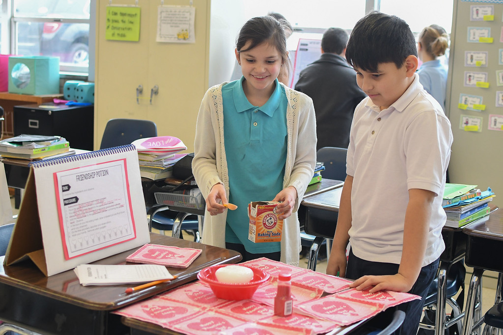 ". Eric Bonzar�The Morning Journal<br> Nine-year-old Bella Davis and 10-year-old Adrian Sams make ""friendship potion,\"" during science class, Feb. 14, 2018."